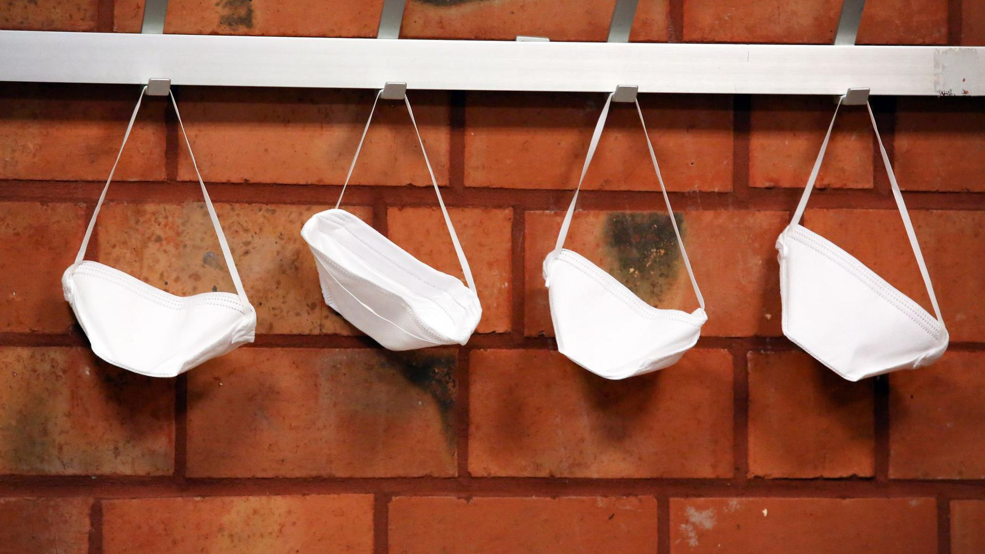 Mund-Nase-Schutzmasken hängen an Haken.