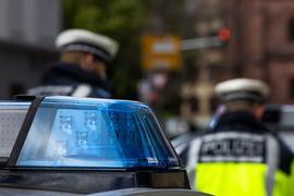 Zwei Polizeibeamte stehen zwischen Einsatzfahrzeugen.