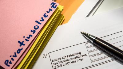 Ein Stift liegt auf einem Antrag für ein Insolvenzverfahren.