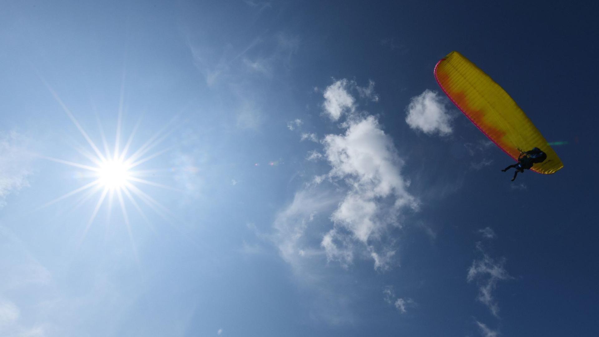 Ein Gleitschirmflieger startet bei sonnigem Wetter.