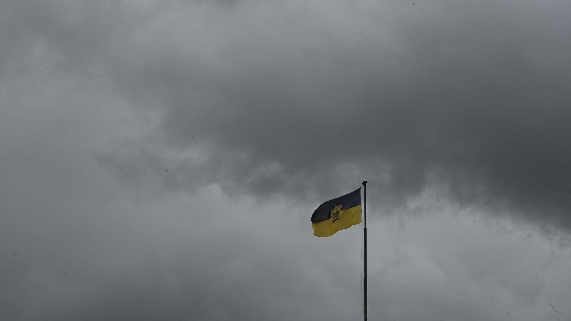 Dunkle Regenwolken über dam Neuen Schloss, auf dem die Flagge von Baden-Württemberg weht.