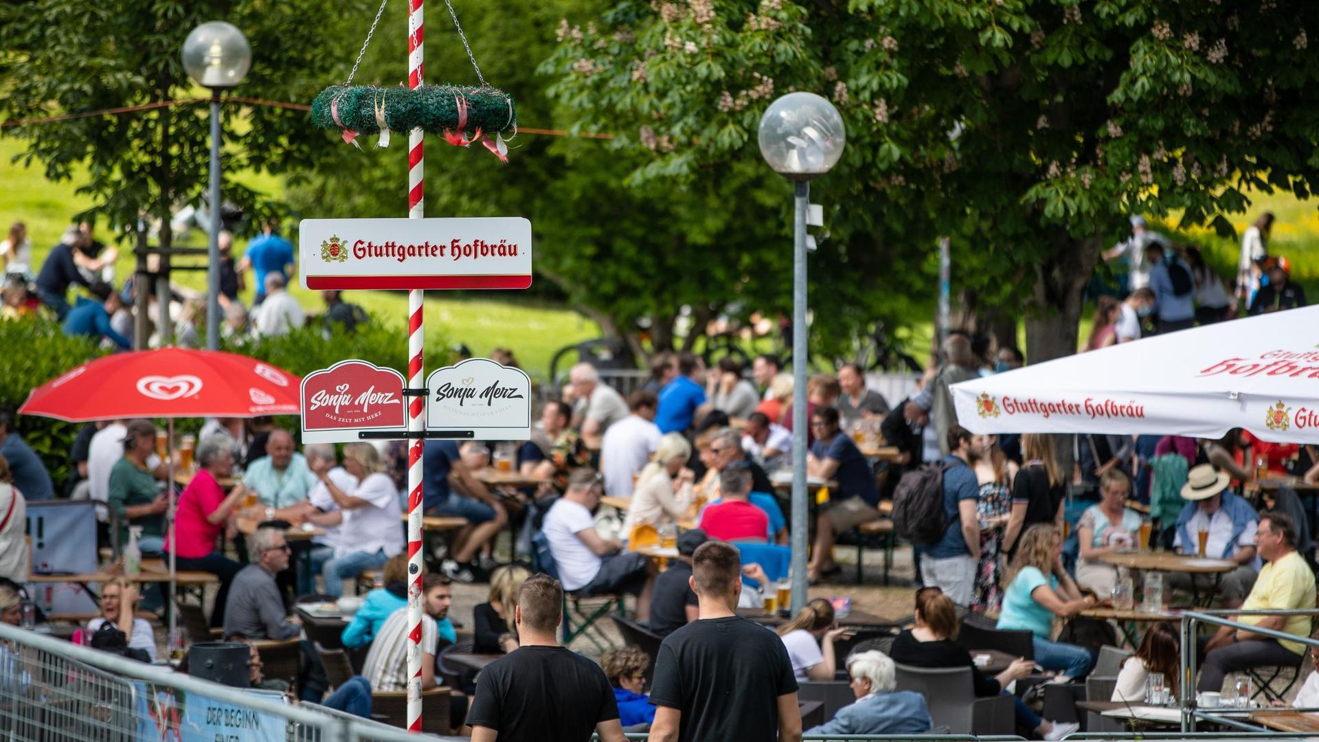 Gäste genießen in einem Biergarten im Schlossgarten das schöne Wetter.
