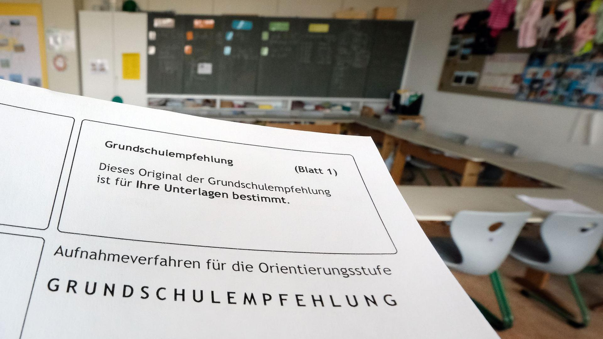 Das Formular einer Grundschulempfehlung wird in einem Klassenzimmer einer Grundschule gehalten.