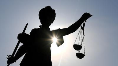 Eine Statue der Justitia mit einer Waage und einem Schwert in ihren Händen.
