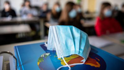EinMund-Nasen-Schutz liegt während des Unterrichts auf einem Atlas.