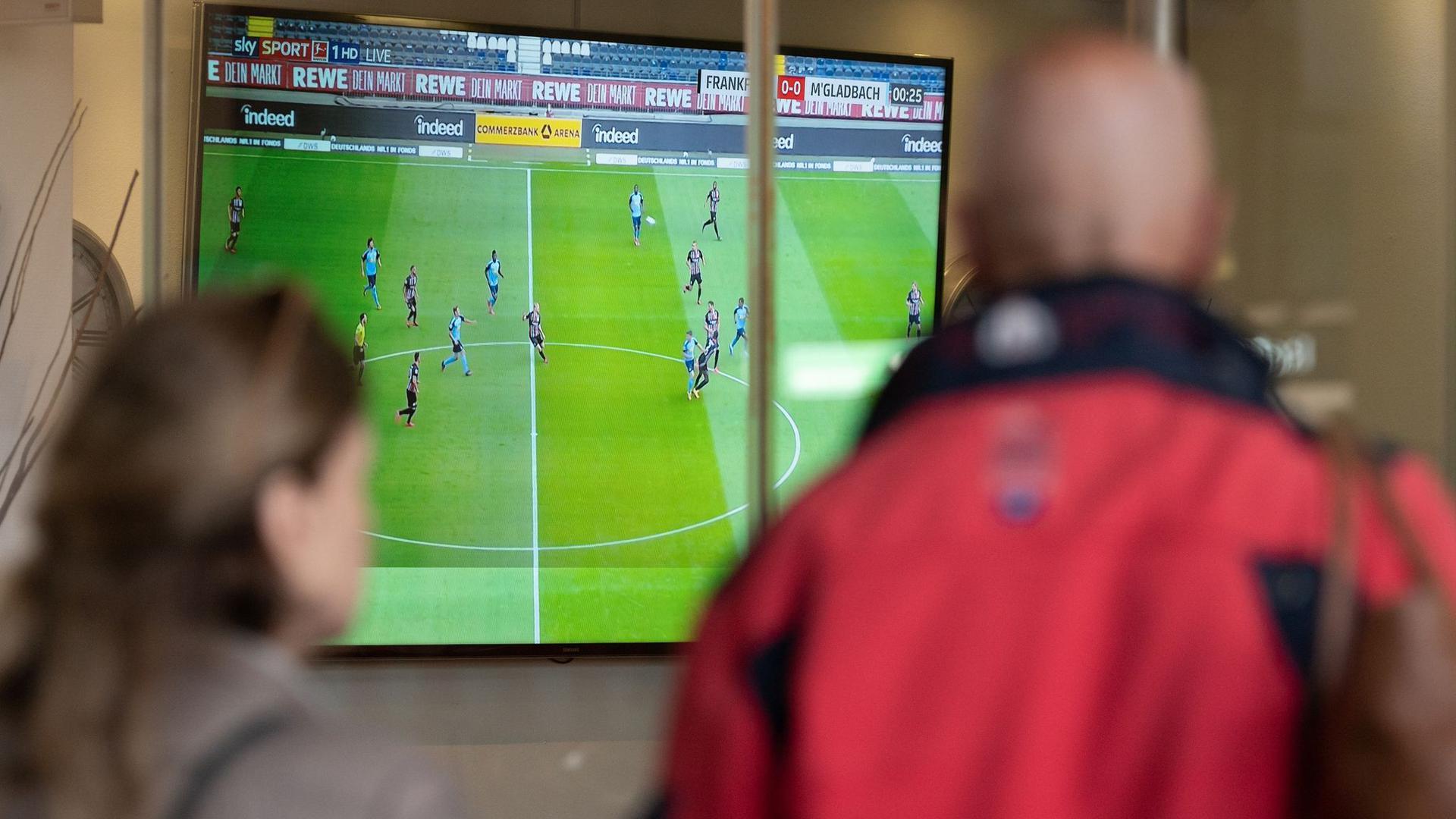 Zwei Menschen verfolgen außerhalb einer Bar ein Fußballspiel.
