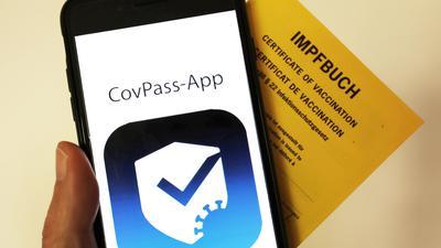 Das Logo der CovPass-App ist neben einem Impfbuch auf einem Smartphone zu sehen.