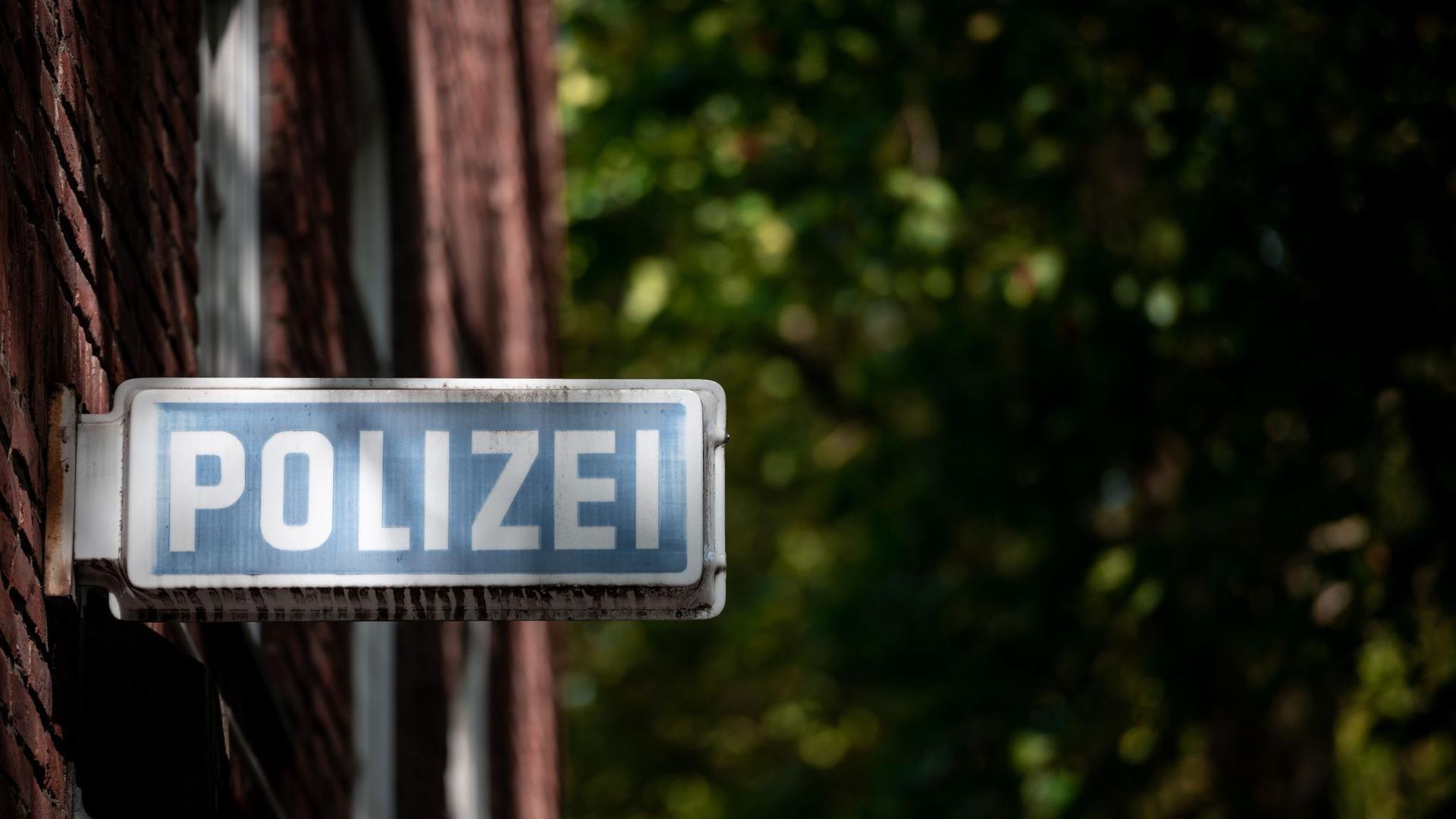 """Ein Schild, auf dem """"Polizei"""" steht, hängt an einer Wache."""