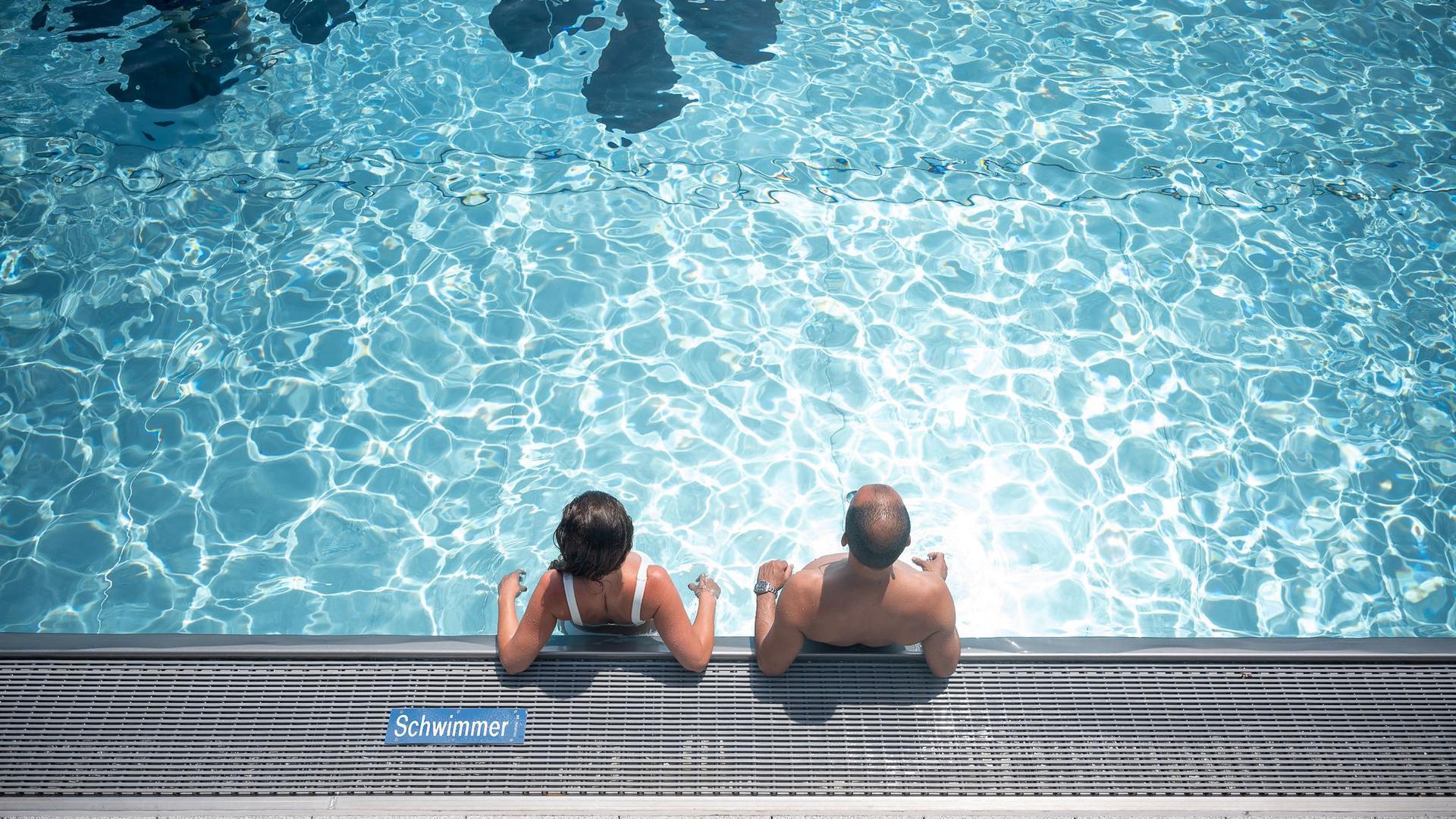 Zwei Badegäste stehen in einem Freibad im Schwimmbecken.