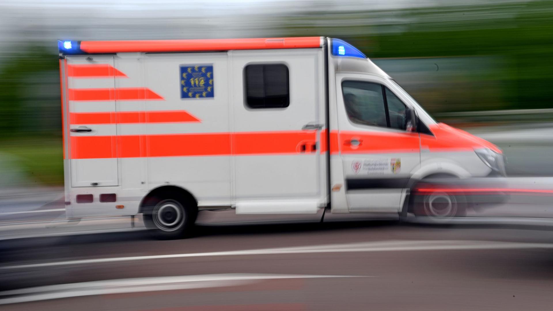 Ein Krankenwagen fährt mit Blaulicht auf einer Straße.