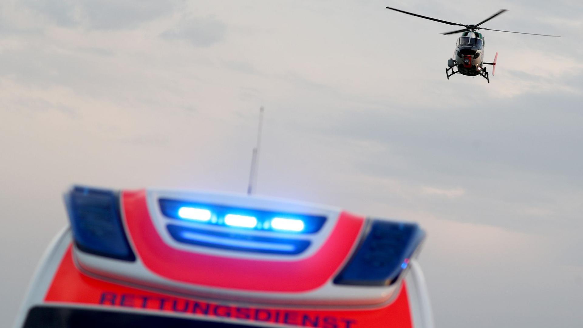 Ein Hubschrauber fliegt über einem Rettungswagen zu einem Unfallort.