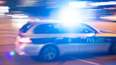 Ein Polizeiauto fährt mit Blaulicht über eine Straße.
