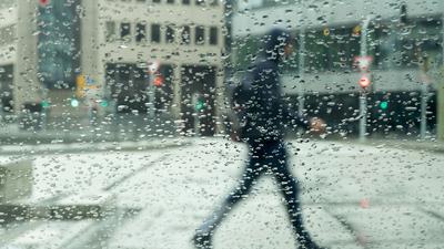 Regentropfen sammeln sich auf einer Autscheibe an der ein Mann vorbeigeht.