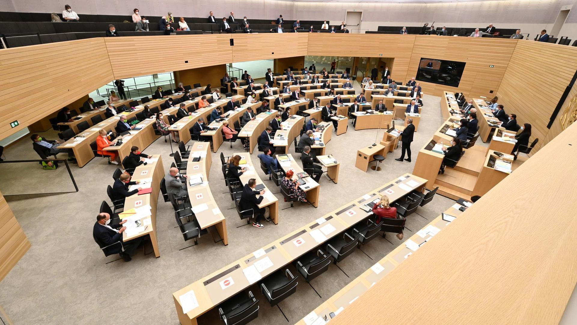 Abgeordnete sitzen im Plenarsaal des Baden-Württembergischen Landtags.