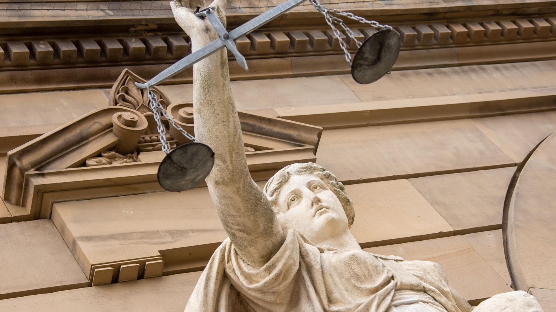 Vor einem Gericht hält eine Statue der Justitia eine Waagschale.