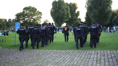 Polizeibeamte gehen über die Neckarwiese.