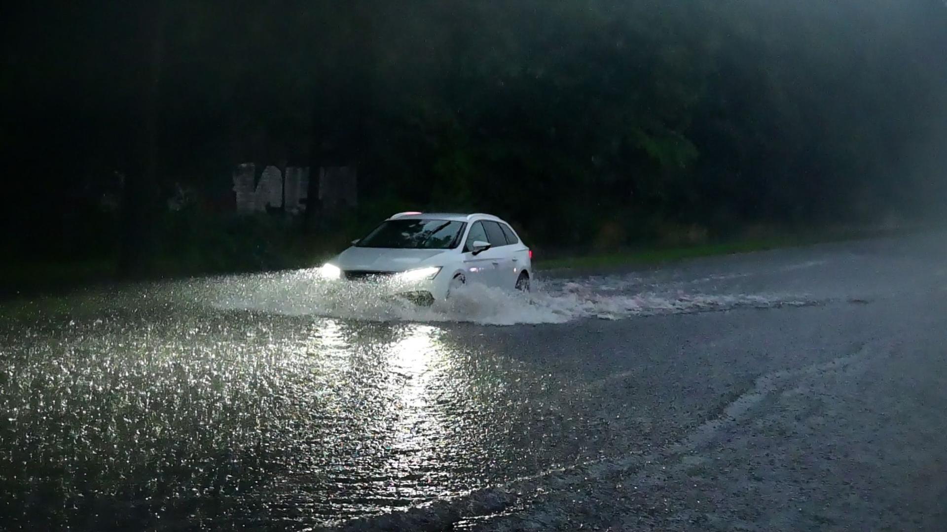Ein Auto fährt durch eine überflutete Straße.