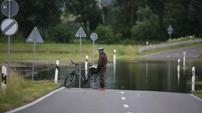 Ein Radfahrer steht an einer überfluteten Straße.