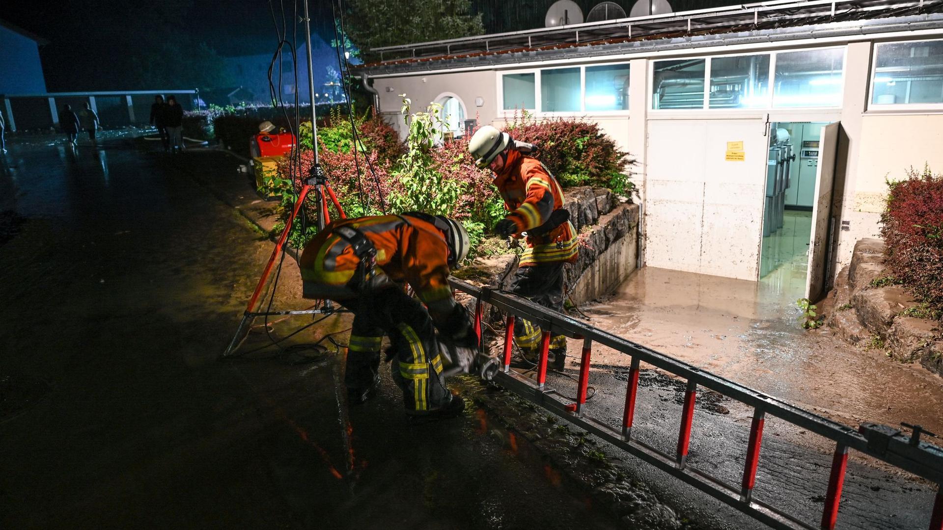 Feuerwehrmänner verlegen einen Schlauch, um einen Keller auszupumpen