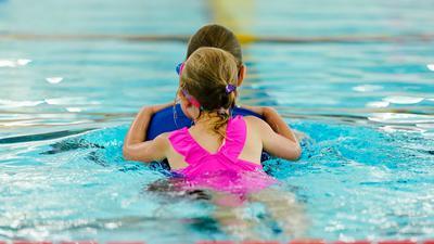 Eine Kursleiterin zieht im Schwimmbad eine Schwimmkurs-Teilnehmerin huckepack durch das Becken.