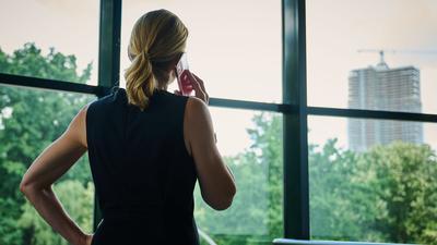 Eine Frau steht in einem Büro am Fenster und telefoniert.