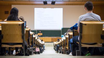 Studentinnen und Studenten sitzen während einer Vorlesung in einem Hörsaal.
