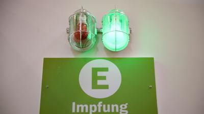 Eine grüne Lampe leuchtet am Eingang eines Corona-Impfzentrums.