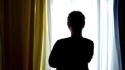 Eine junge Frau steht in einem Zimmer eines Frauenhauses.