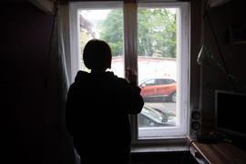 Eine Jugendliche sitzt in einem abgedunkelten Zimmer.