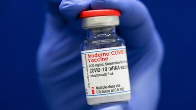 Eine Ampulle mit Covid-19-Impfstoff wird in einer Hand gehalten.