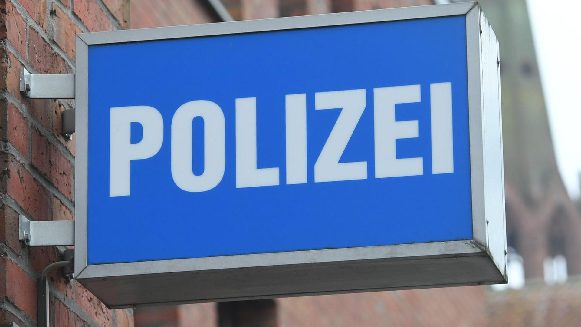 """Ein Schild mit dem Schriftzug """"Polizei"""" hängt an einer Polizeiwache."""