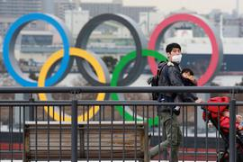 Ein Mann läuft an den Olypischen Ringen vorbei.