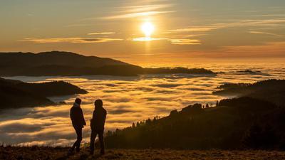 Zwei Spaziergänger betrachten den Sonnenuntergang über dem Wolkenmeer.