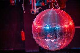 Eine farbig beleuchtete Discokugel dreht sich über der Tanzfläche in einer Diskothek.