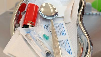 Im Drogenkonsumraum wird eine Schale gezeigt, in der sich Utensilien für den intravenösen Drogenkonsum befinden.