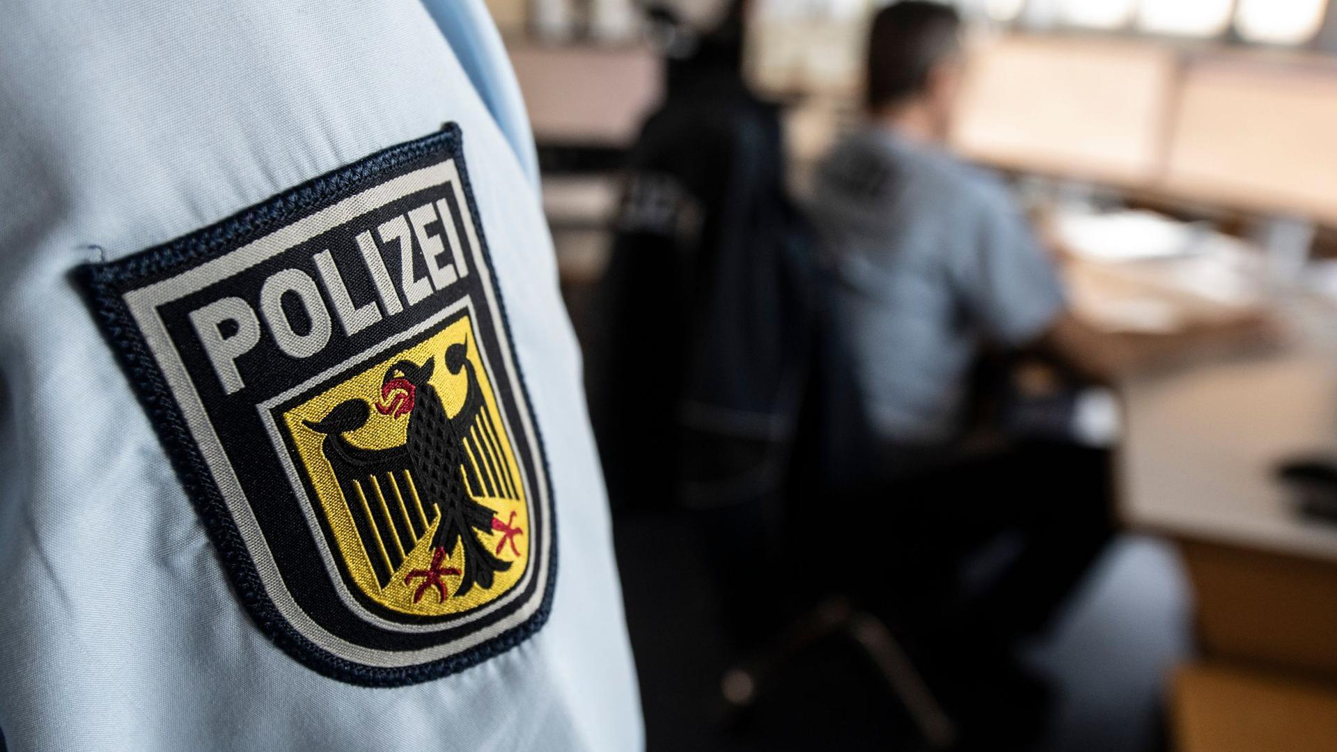 Ein Polizist der Bundespolizei steht in einer Leitstelle.