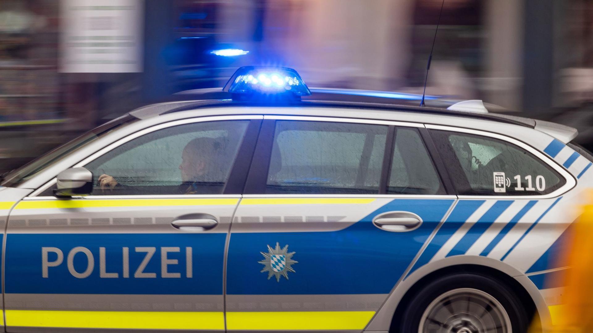 Ein Fahrzeug der Polizei fährt mit Blaulicht durch die Innenstadt.