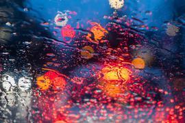 Regentropfen sind auf einer Autoscheibe zu sehen.