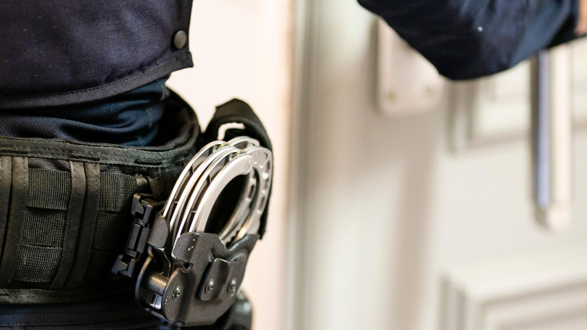 Handschellen sind an einem Gürtel eines Justizvollzugsbeamten befestigt.