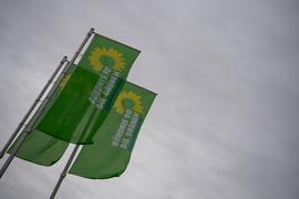 Flaggen mit dem Logo von Bündnis 90/Die Grünen wehen vor einem Veranstaltungszentrum.