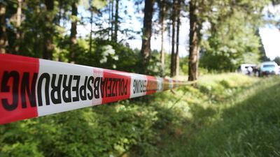 Ein Absperrband der Polizei ist in einem Waldstück angebracht.