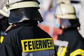 Einsatzkräfte der Feuerwehr in Schutzkleidung.
