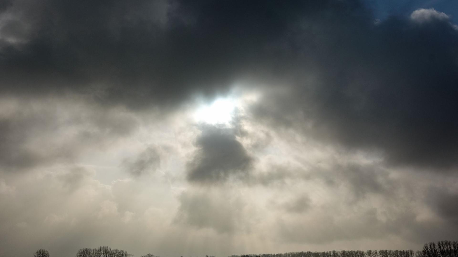 Die Sonne kommt nur kurzzeitig hinter einer dunklen Wolkendecke hervor.