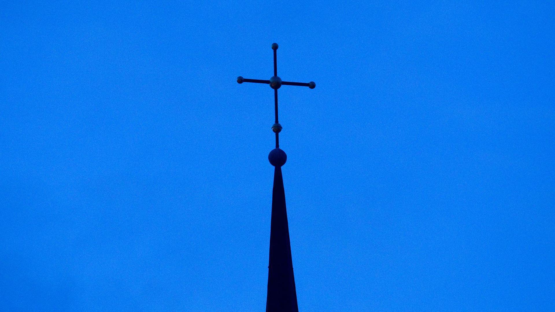 Das Kreuz einer Kirche ist in der Abenddämmerung zu sehen.
