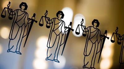Die Justitia ist an einer Scheibe am Eingang zum Oberlandesgericht zu sehen.