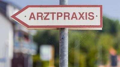"""Ein Schild """"Arztpraxis"""" steht an der Straße."""