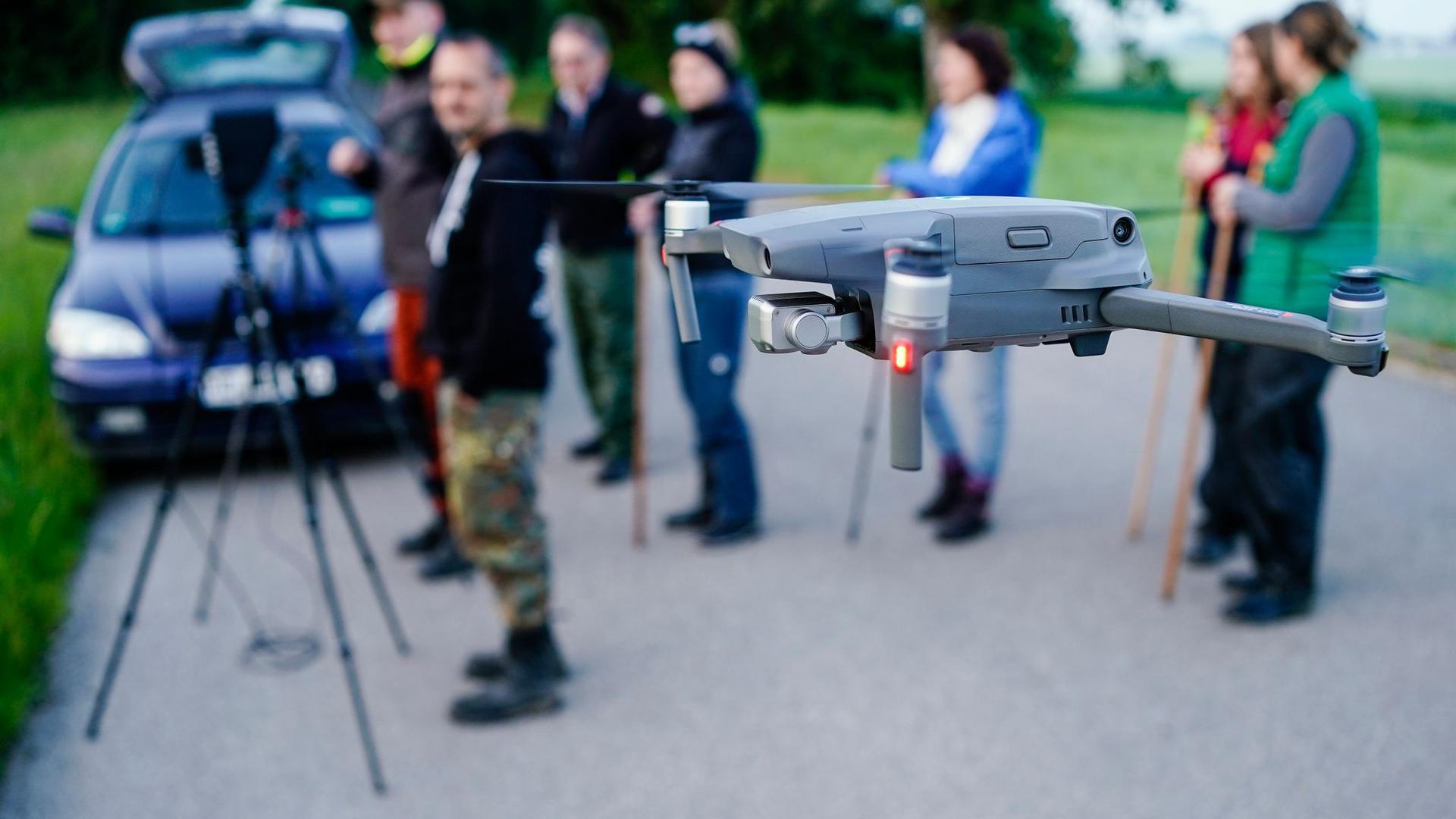 Helfer der Rehkitz-Rettung stehen hinter einer sich im Flug befindlichen Drohne mit Wärmebildkamera.