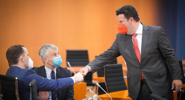 Hubertus Heil (r, SPD), Bundesminister für Arbeit und Soziales, begrüßt Jens Spahn (l, CDU), Bundesminister für Gesundheit, vor Steffen Bilger, Parlamentarischer Staatssekretär beim Bundesminister für Verkehr und digitale Infrastruktur.