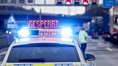 """Auf einem Polizeifahrzeug leuchtet die Aufschrift """"Gesperrt""""."""