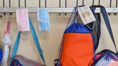 Masken und Taschen hängen in einer Grundschule an Kleiderhaken.